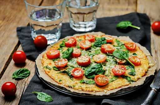 Cauliflower pizza crust with tomato and spinach 641084598