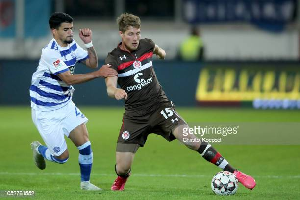 Cauly Oliveira Souza of Duisburg challenges for the ball with Daniel Buballa of St Pauli during the Second Bundesliga match between MSV Duisburg and...