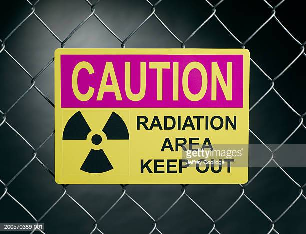 """""""Caution, radiation area, keep out"""" sign on fence"""