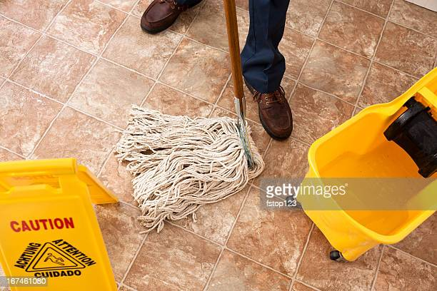 Caution sign, janitor man mopping floor of retail store. Cleaning.
