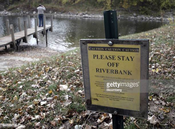 Caution sign warns visitors to stay off the riverbank because of elevated dioxin levels as Gary Henry takes a picture of the Tittabawassee River at...