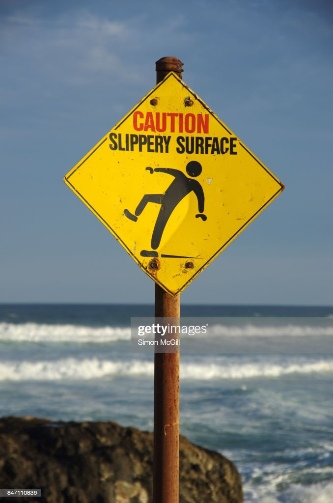 'Caution Slippery Rocks' warning sign next to Sawtell Memorial Rock Pool, Sawtell, New South Wales, Australia : Stock Photo