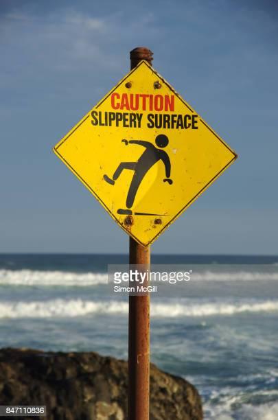 'Caution Slippery Rocks' warning sign next to Sawtell Memorial Rock Pool, Sawtell, New South Wales, Australia