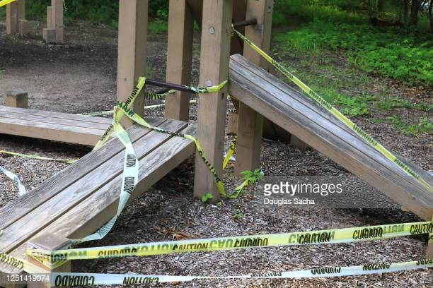 caution tape and barricade on outdoor fitness equipment warning of coronavirus pandemic closure - governor stock pictures, royalty-free photos & images