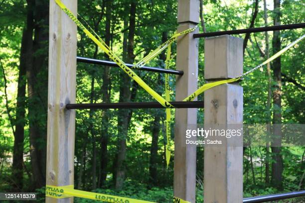 caution tape and barricade on outdoor playground equipment warning of covid-19 pandemic closure - governor stock pictures, royalty-free photos & images