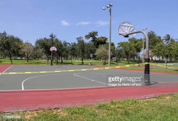 caution tape around outdoor basketball court - cordon tape stock pictures, royalty-free photos & images