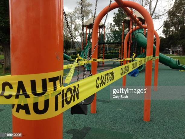 caution tape around swing set in closed play area due to coronavirus pandemic - アゴーラヒルズ ストックフォトと画像