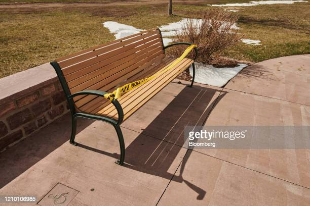Caution tape blocks visitors from seating on a bench at Falls Park in Sioux Falls South Dakota US on Wednesday April 15 2020 South Dakota Governor...