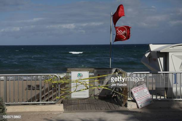 Caution tape closes off an entrance to the beach and a lifeguards no swimming flag flies above as Palm Beach County officials announced that all...