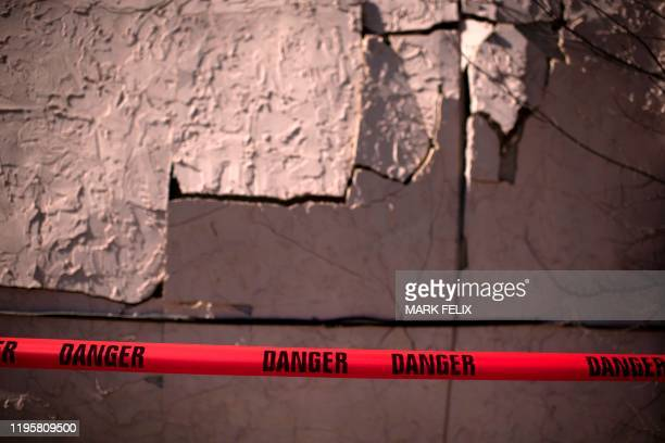 Caution tape is put across the side of a damaged home after explosion at a northwest Houston Texas manufacturing business on January 24 2020 A large...