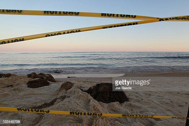 Caution tape is seen around absorbent material laying on the beach as oil washes ashore from the Deepwater Horizon oil spill in the Gulf of Mexico on...