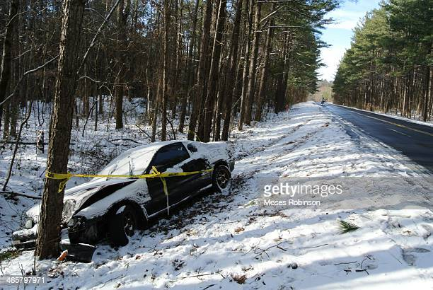 Caution tape is wrapped around a vehicle that crashed into a tree after the driver lost contol yesterday during a winter storm on January 29 2014 in...