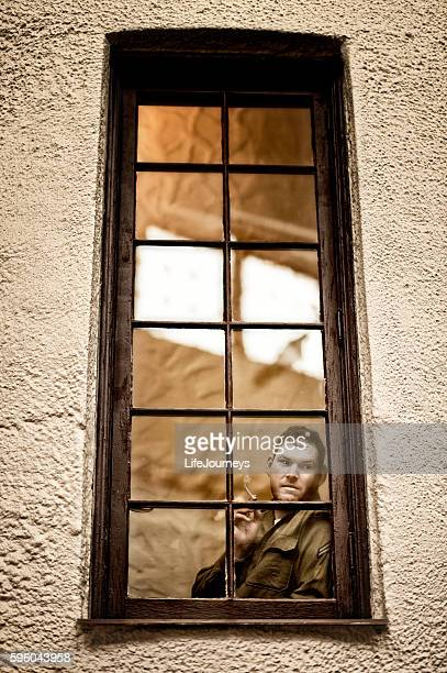 Cautious WWII American Soldier Standing Behind A Window Pane Watching
