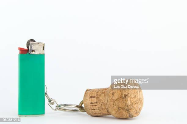 cava cork keyring holding green cigarette lighter - cork stopper stock photos and pictures