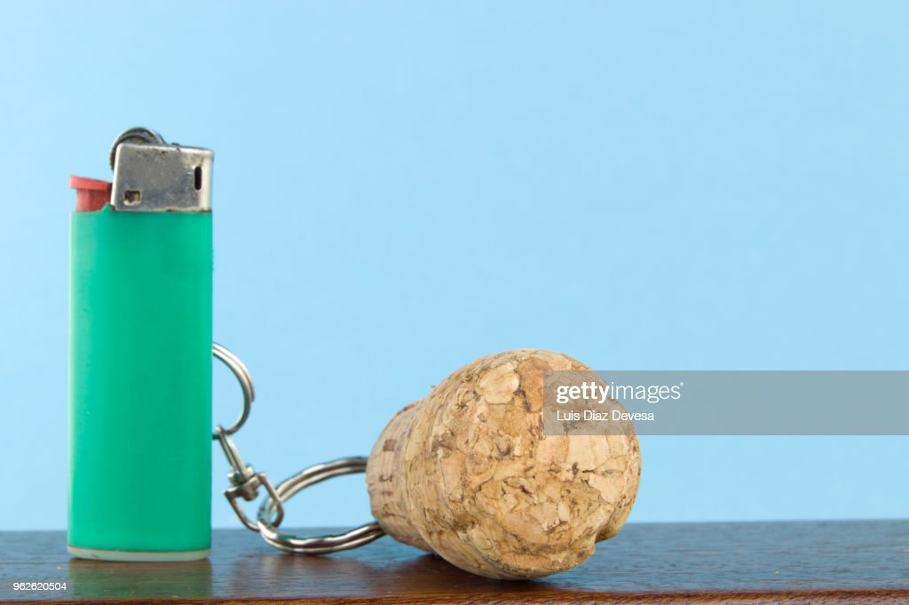 Cava cork keyring holding green cigarette lighter : Stock Photo