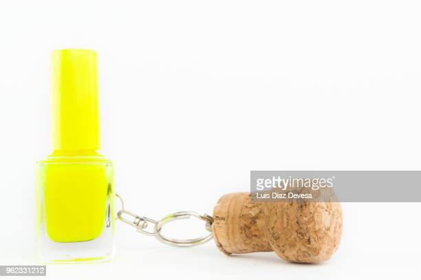 cava cork keyring holding  yellow nail polish - bottle stopper stock photos and pictures