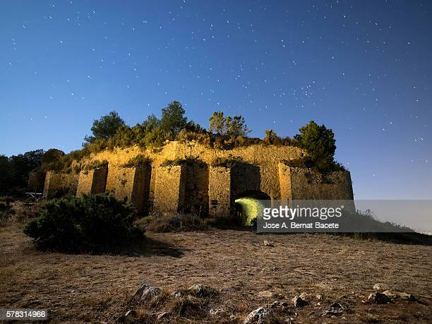 Cava or snowfield, medieval building on top of a mountain overlooking midnight