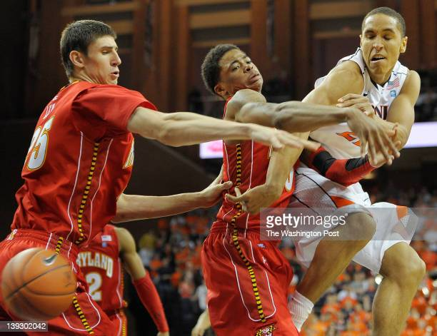 Cavaliers guard Malcolm Brogdon right passes off under the basket against Terrapins guard Nick Faust center and Terrapins center Alex Len left as the...