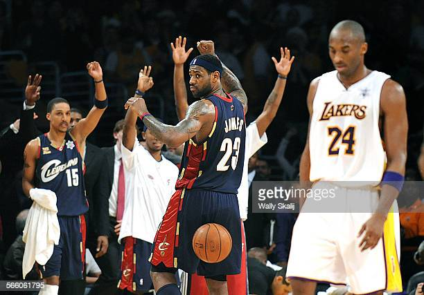 Cavaliers LeBron James celebrates what he thought was a three–pointer at the buzzer as Lakers Kobe Bryant walks of the court at halftime at the...