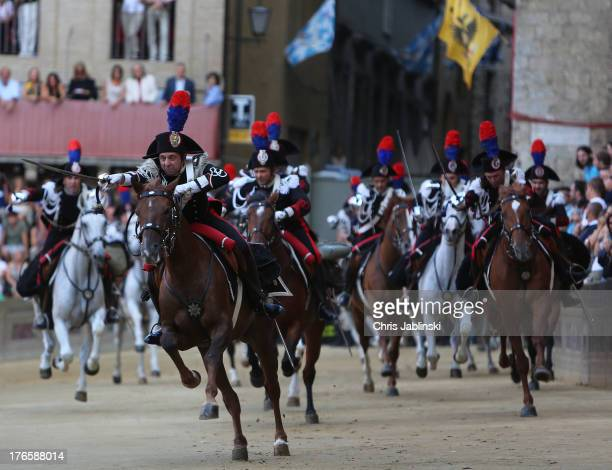 Cavalry horsemen ride a course before the main rehearsal of the Palio at the Piazza del Campo on August 15 2013 in Siena The Palio races in Siena in...