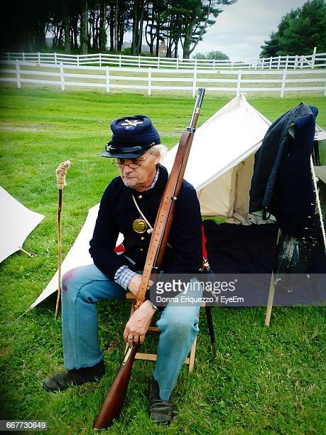 cavalry soldier sitting by tent on grassy field - historical reenactment stock pictures, royalty-free photos & images