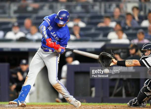 Cavan Biggio of the Toronto Blue Jays swings and his bat appears to hit the catcher's mitt of Gary Sanchez of the New York Yankees as Biggio was...