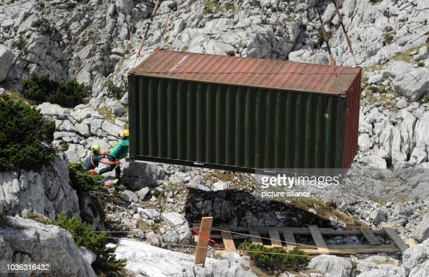 A cave and mountain rescue team push a container into the right position with the help of a helicopter near the entrance to the Riesending cave on...
