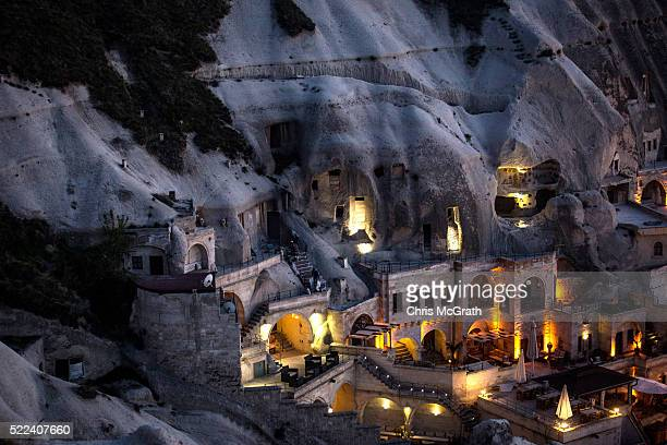 A cave hotel is seen at sunset in the town of Goreme on April 17 2016 in Nevsehir Turkey Cappadocia a historical region in Central Anatolia dating...