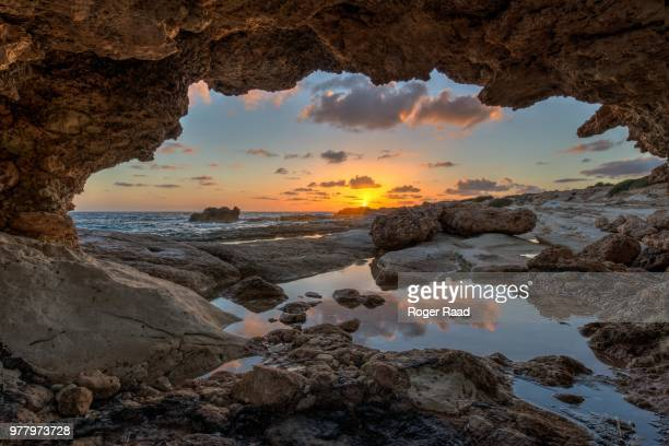 cave on seashore at sunset, cyprus - cyprus stockfoto's en -beelden