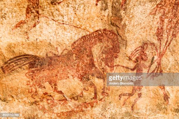 Cave painting  from the upper paleolithic age of a man leading a horse at the World Heritage Bhimbetka rock shelters in Madhya Pradesh, India