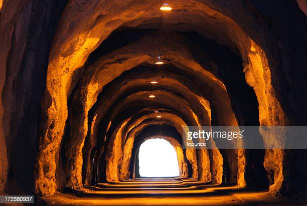 Cave-like tunnel with white light at end
