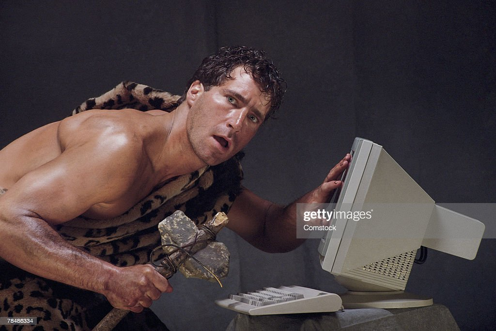 Caveman baffled by computer : Stock Photo