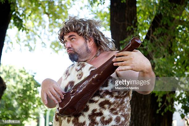 caveman playing club - prehistoric man stock pictures, royalty-free photos & images
