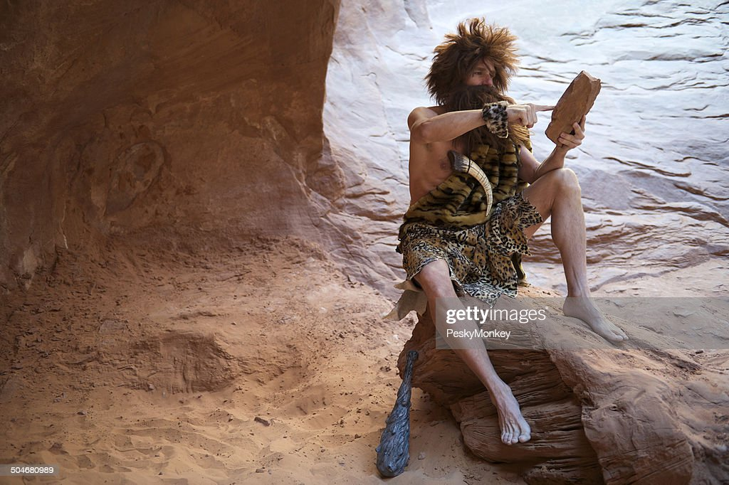 Caveman Sitting Outdoors Using Stone Tablet with Touchscreen : Stock Photo