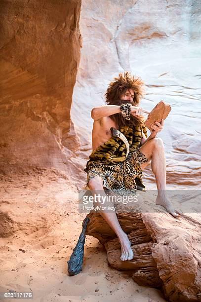 Homme des carvernes assis à l'extérieur en utilisant une tablette à écran tactile de Pierre
