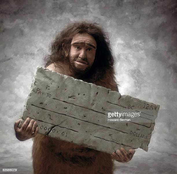 caveman with check - caveman stock pictures, royalty-free photos & images
