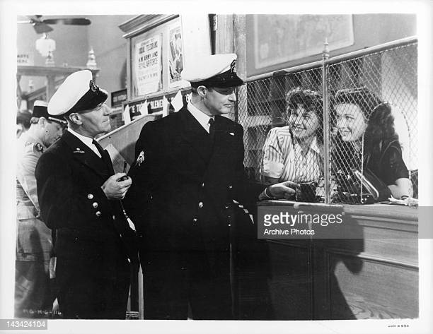 Caven Watson accompanies Robert Donat to send cable to his wife Clerks Michele Fraser and Christianne de Maurin smile as he asks them to add the word...