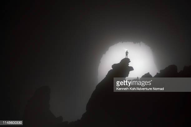 a caver stands on the 'hand of dog' stalagmite, backlit by the 1st doline, inside the world largest cave in vietnam - spelunking stock pictures, royalty-free photos & images