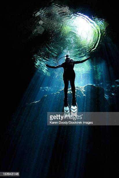 A cavern diver ascends into the light filtering into cenote system at Yucatan Peninsula, Mexico.