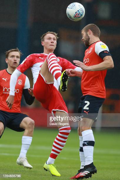 Cawley Woodrow of Barnsley challenged by Martin Cranie of Luton Town during the Sky Bet Championship match between Luton Town and Barnsley at...