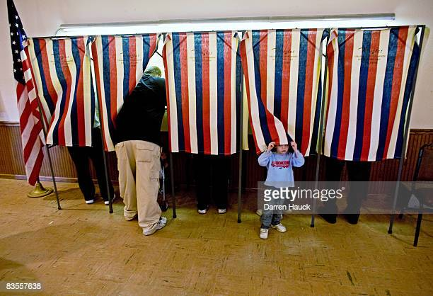 Cayden Andrews peaks out from the voting booth as his father Josh Andrews casts his vote at the Town Hall November 4 2008 in Saukville Wisconsin This...