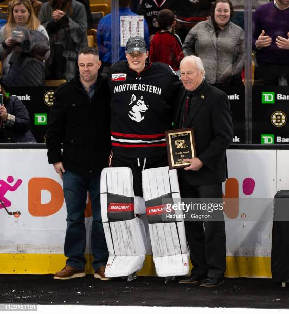 Cayden Primeau of the Northeastern Huskies accepts the Eberly Award from Dan Eberly and his son Danny Eberly after a game against the Boston College...
