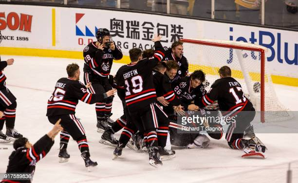 Cayden Primeau of the Northeastern Huskies celebrates with his teammates Eric Williams, Matt Filipe and Biagio Lerario after a game against the...