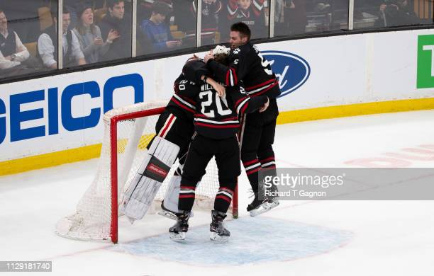 Cayden Primeau of the Northeastern Huskies celebrates with teammates Ryan Shea and Eric Williams after a victory against the Boston College Eagles...