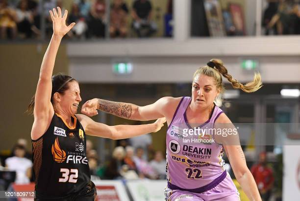 Cayla George of the Boomers drives to the basket past Mikaela Cocks of the Fire during the round 15 WNBL match between the Townsville Fire and the...