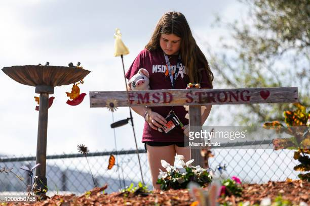 Cayley Clemo a Coral Springs Middle student, visits a makeshift memorial outside of Marjory Stoneman Douglas High School in Parkland, Fla., on...