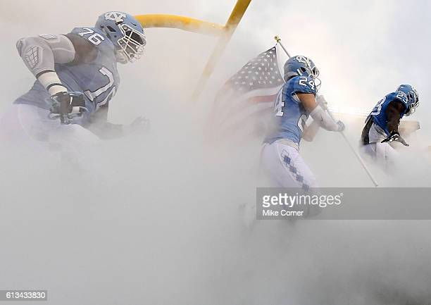 Cayson Collins Ayden Bonilla and RJ Prince of the UNC Tar Heels take the field against the Virginia Tech Hokies at Kenan Stadium on October 8 2016 in...