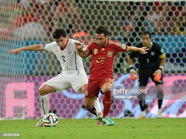 Cazorla of Spain vies for the ball with Mena of Chile during the 2014 FIFA World Cup Group B soccer match between Spain and Chile at the Maracana...