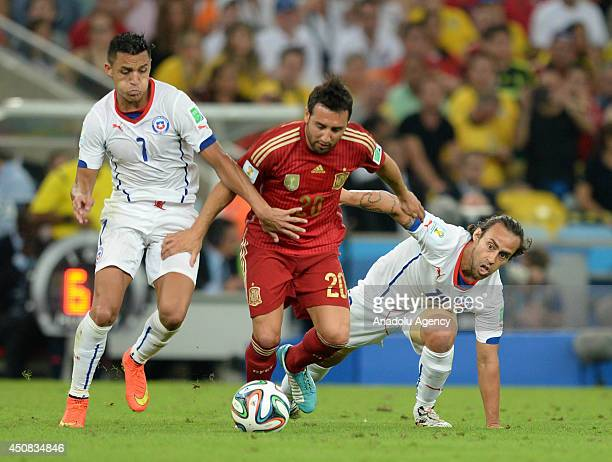 Cazorla of Spain vies for the ball with Valdivia and Alexis of Chile during the 2014 FIFA World Cup Group B soccer match between Spain and Chile at...