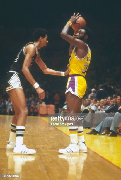 Cazzie Russell of the Los Angeles Lakers looks to pass the ball over the top of George Gervin of the San Antonio Spurs during an NBA basketball game...